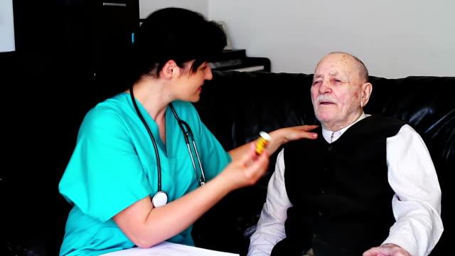 Nurse giving pills to a senior man video