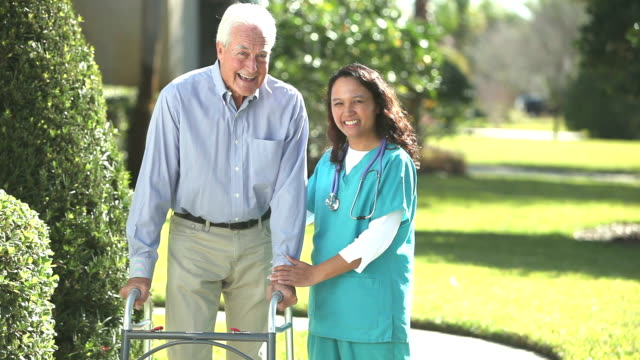 Nurse helping senior man using a walker outdoors video