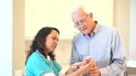 Nurse helping senior man with prescription medicine video
