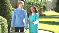 Nurse helping senior woman using a walker outdoors video