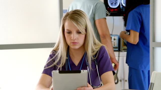 nurse in clinic using tablet pc looks and smiles video