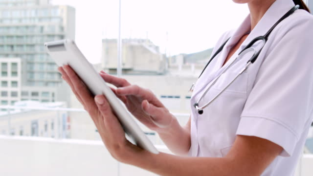 Nurse in tunic using tablet pc and smiling at camera video