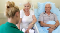 Nurse notes the state of health of senior male patient video