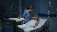 DS Nurse observing a female patient lying in the intensive care unit video