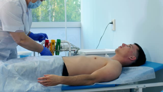 Nurse preparing male patient for ECG test video