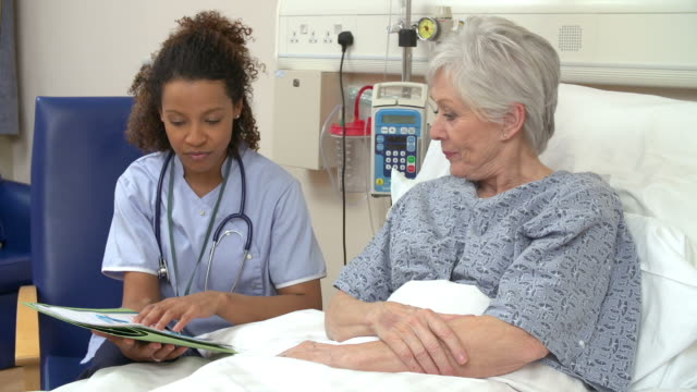 Nurse Sitting By Male Patient'Nurse Sitting By Senior Female Patient's Bed In Hospitals Bed In Hospital video