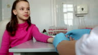 Nurse takes blood from a finger of child in medical laboratory video