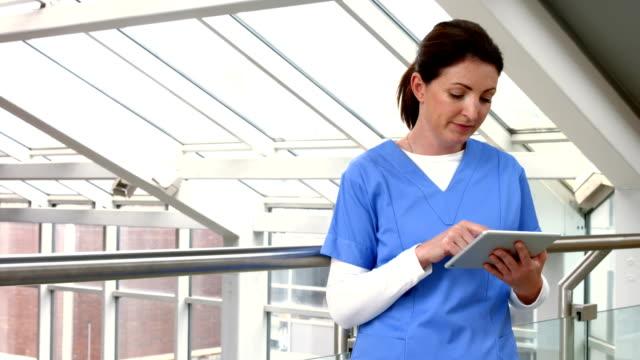 Nurse using tablet pc in hallway video