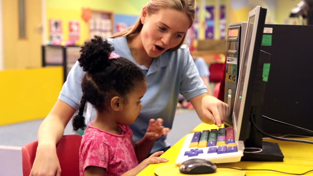 Nursery worker teaching child how to use a computer keyboard video