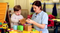 Nursery worker with child playing with toys video