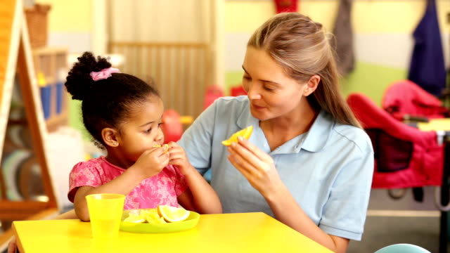 Nursery workers with child eating oranges video