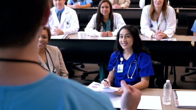 Nurses, doctors, and medical students listening to speaker at healthcare conference video