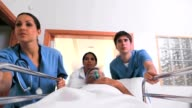 Nurses driving a patient on his bed with an oxygen mask video