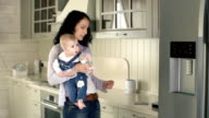 Nursing a BClose up of attractive woman holding in arms her child and a feeding bottle and trying to make a telephone callaby video