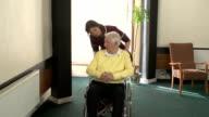 Nursing Care Home - Pushing elderly man in Wheelchair video