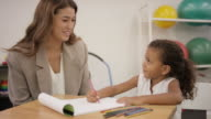 Occupational therapist working with child patient in clinic video