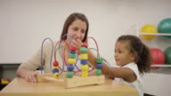 Occupational therapist working with young girl in clinic video