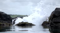 CLOSE UP: Ocean water wave crushing violently against rough rocky wall video