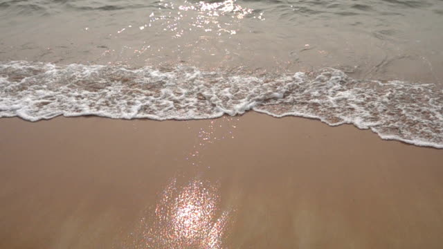 Ocean wave breaking at the beach during sunset in slow motion video