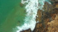 AERIAL: Ocean waves splashing into rocky shore below the cliff video
