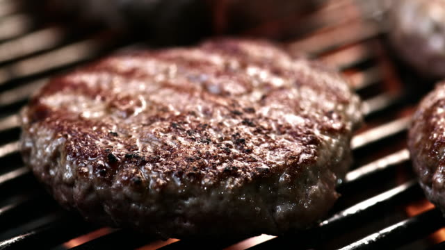 SLO MO LD of beef burger sizzling on a grill video