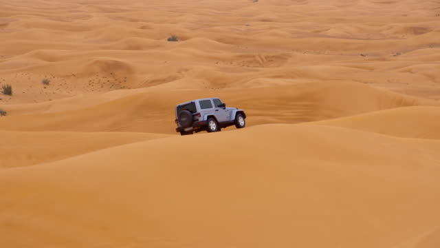 SLO MO Off road car driving over a sand dune video