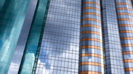 office building exterior reflects fast motion of clouds in sky, time lapse. video