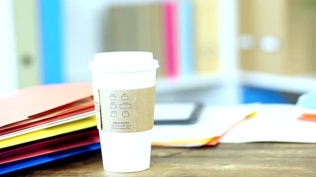 Office desk with file folders, cup of coffee, digital tablet and cell phone video
