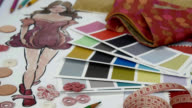 Office table of Fashion designer & Tailor working with sketch of clothes, samples/ garment business concept video