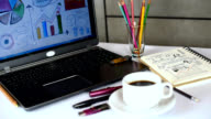 Office table with laptop, analyzing graphic, notebook, cup of coffee / business conceptual video
