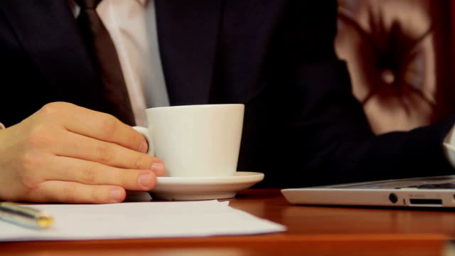 Office worker drinking coffee, checking information on laptop video