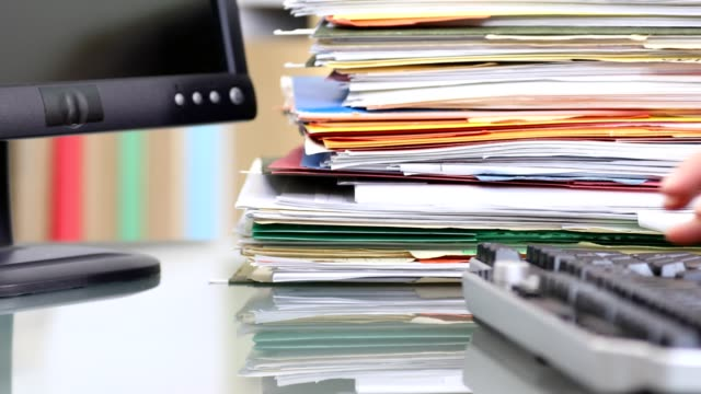 Office worker typing on computer keyboard, pile of folders. video