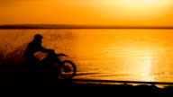 Off-road motorbike extreme cornering. Motorcyclist at sunset near the river. Extreme motocross bike, dirt from under the wheels video