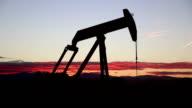 Oil derrick pumps crude sunset Larimer County Colorado Rocky Mountains video