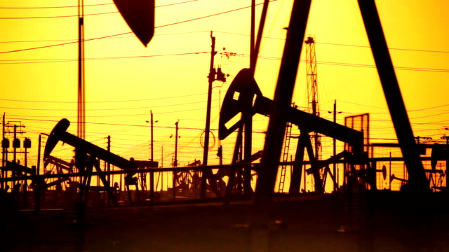 Oil Drilling in Silhouette at Sunset video