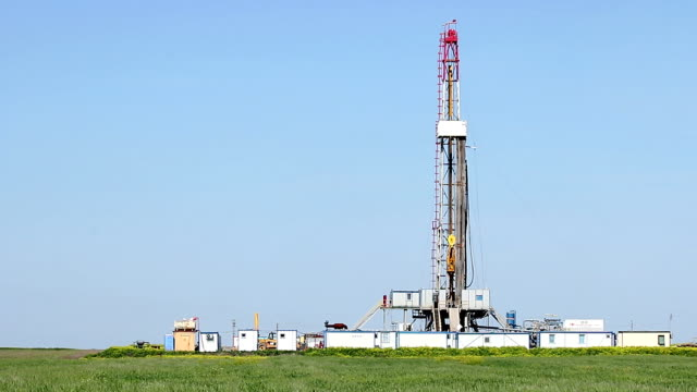 oil drilling rig on green wheat field video