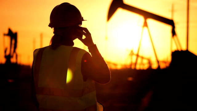 Oil Production Engineer on Site at Sunset video