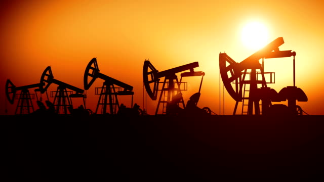 Oil Pumps in a Row at Sunset. Looped 3d animation. Technology and Industrial Concept. video