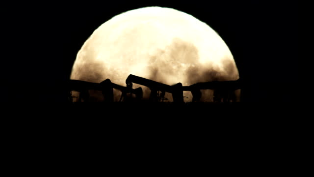 Oil Pumps Silhouette on a Full Moon Background in a Polluted Environment video