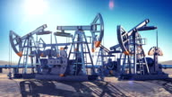 Oil Pumps Working in the Desert. Bright Sun Shining on Blue Sky. Looped 3d animation. HD 1080. Industrial and Technology Concept. video