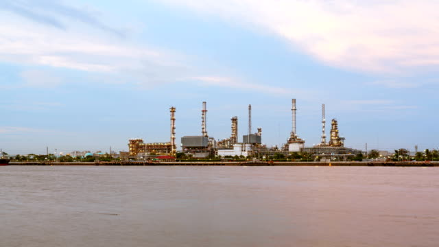 Oil Refinery or Oil Industry in front of Chao Phraya River, and sky sunset Day to night and ship transportation and factory concept High quality in HD Timelapse video