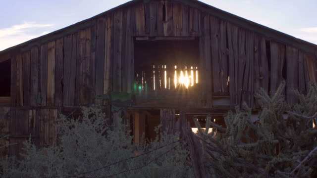 Old abandoned barn with sun light streaming through open beams video
