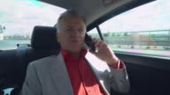 Old - aged boss has phone conversation with business partner on the way to work video