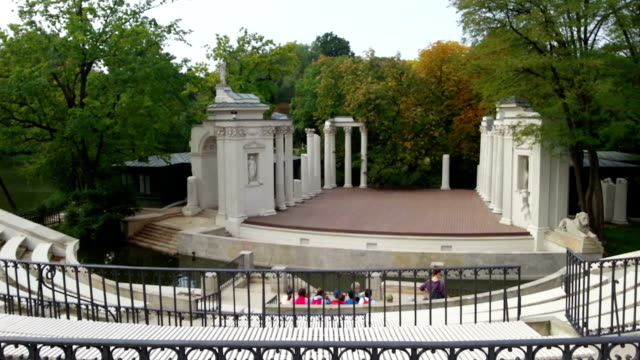 Old amphitheater in Lazienki Park, Warsaw. Group of tourists sitting video