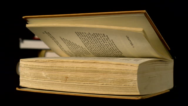 Old book falling on black background, Slow Motion video