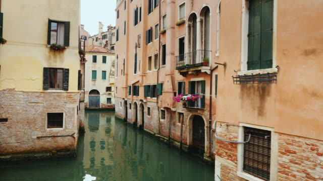 Old buildings and a narrow canal for boats and gondolas in Venice. A typical example of the architecture of Venice video