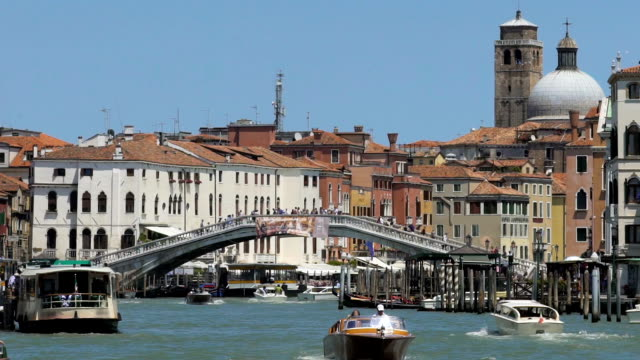Old city with narrow channel full of speedboats, people crossing bridge over it video