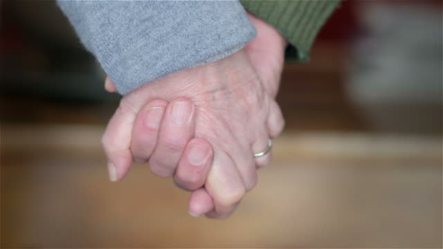 Old couple holding hands video