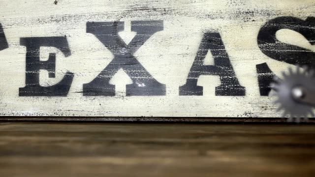 Old cowboy boots and spurs with Texas sign in background. video