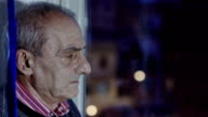old depressed man looking out the window with night city lights in background video